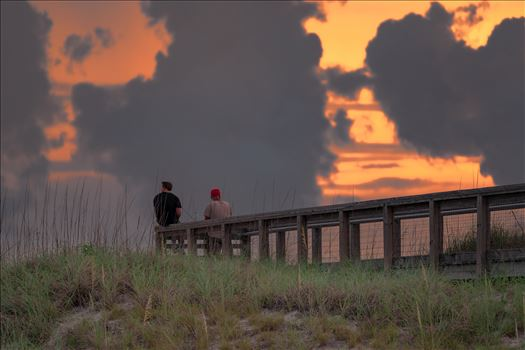 Two guys watching the sunset from the lookout at St. Andrews State Park, Panama City Beach, Florida